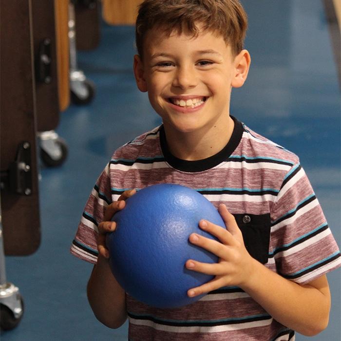 Photo of smiling boy holding blue ball